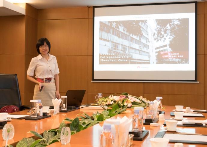 Ада Ксу, PR-директор потребительских продуктов Huawei показывает фотографию здания, где основатель Huawei снял первый офис фирмы — комнату площадью примерно 10 м кв.